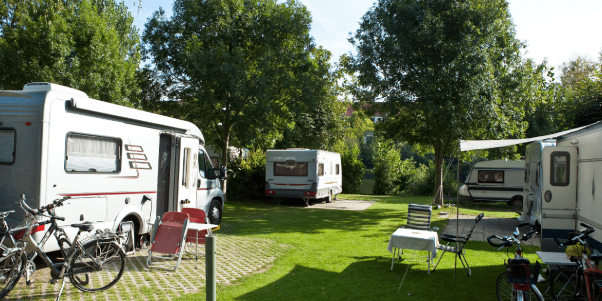 4 RVs parked in a circle at an RV park with grass between and surrounded by trees