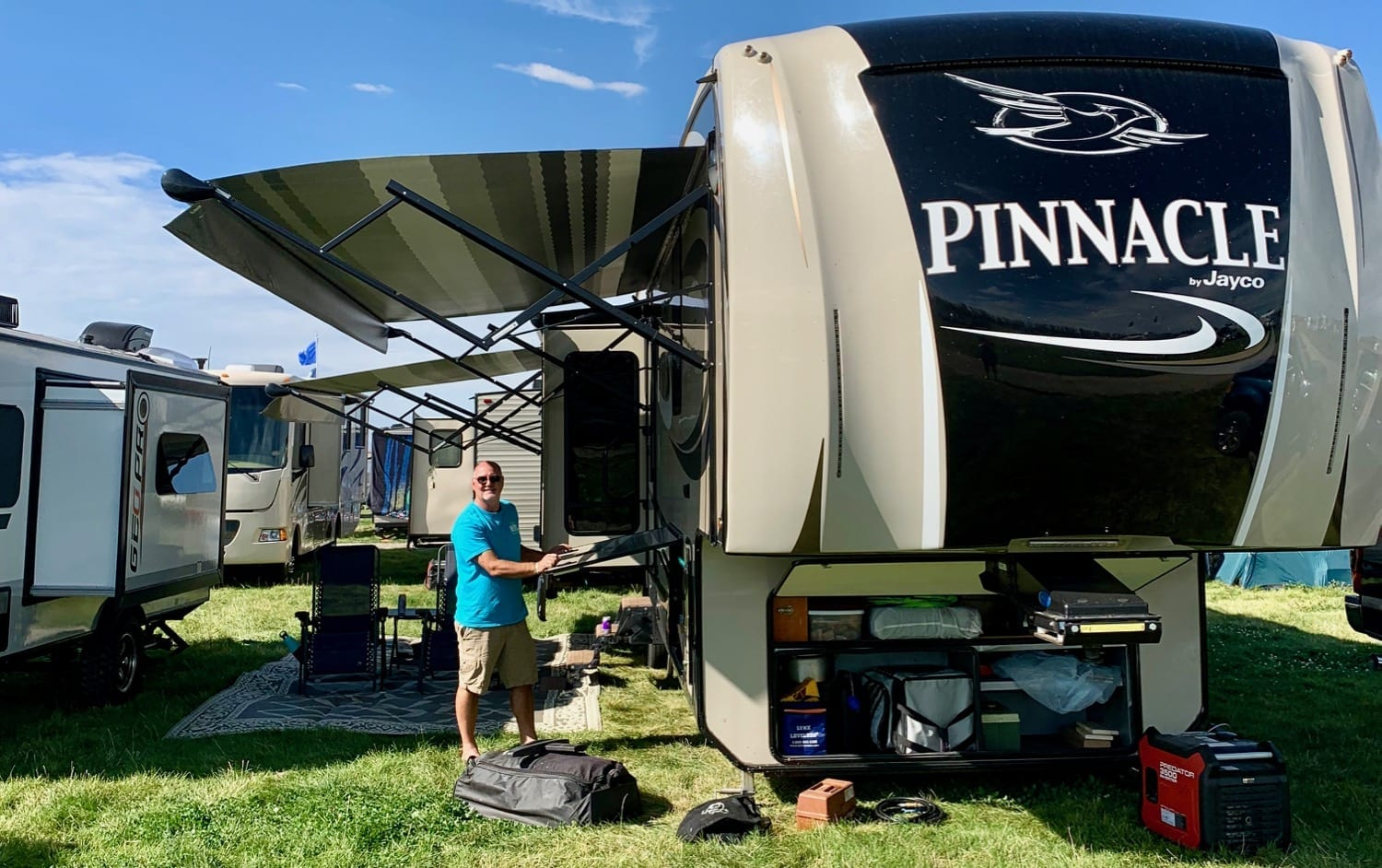 RV parked on grass with many other RVs. Man opening basement compartment under RV awning.