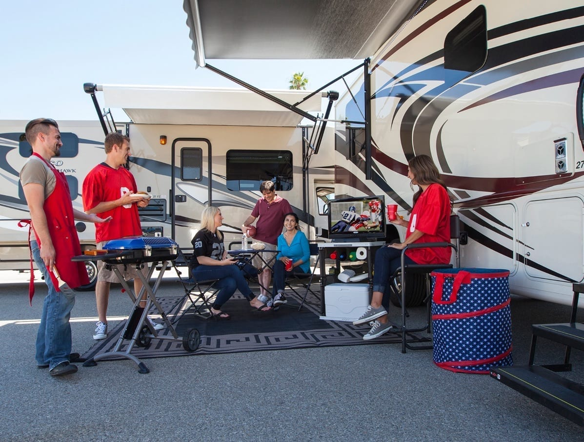 football outdoor tailgating get together with people, grills and food under RV awning.