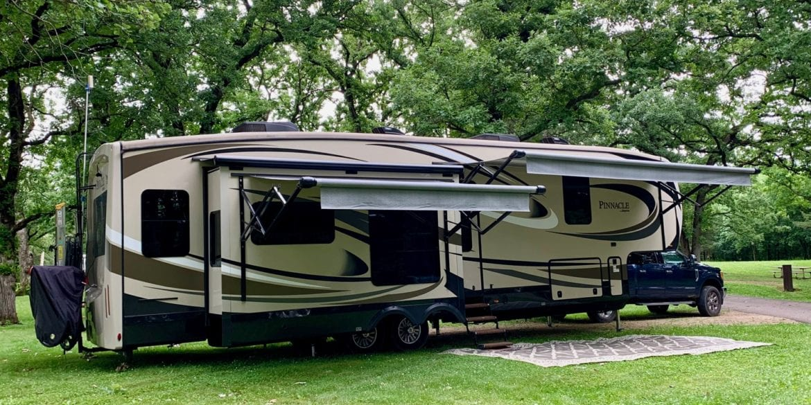 jayco pinnacle FBTS at campsite under trees with awnings out.