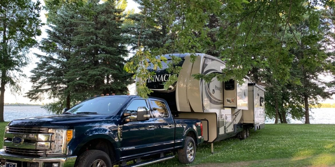 Ford truck attached to Jayco Pinnacle FBTS parked by a lake under trees