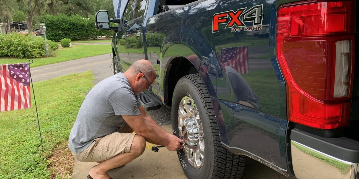 man checking tire pressure on Ford truck attached to fifth wheel
