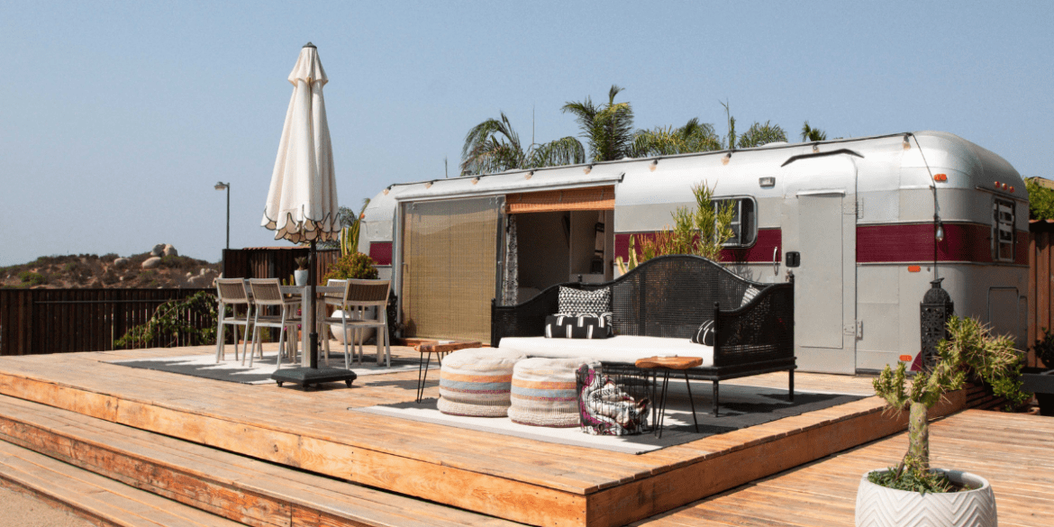 vintage airstream being used as guest suite in backyard with deck off front and door open to inside.