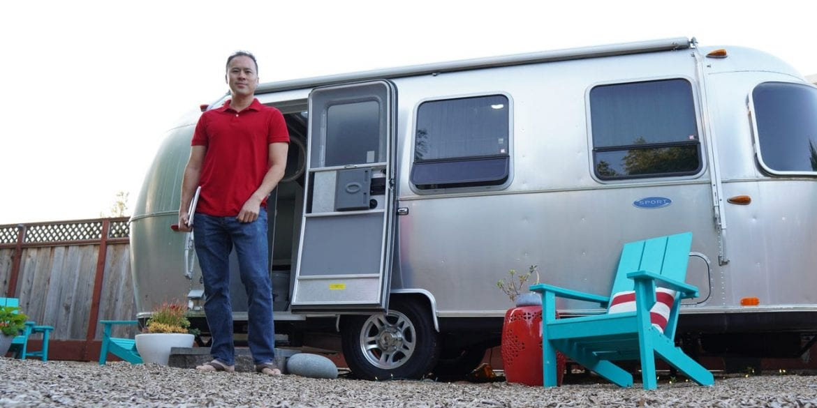 Man in front of RV home office in backyard with blue chair out front siting on gravel