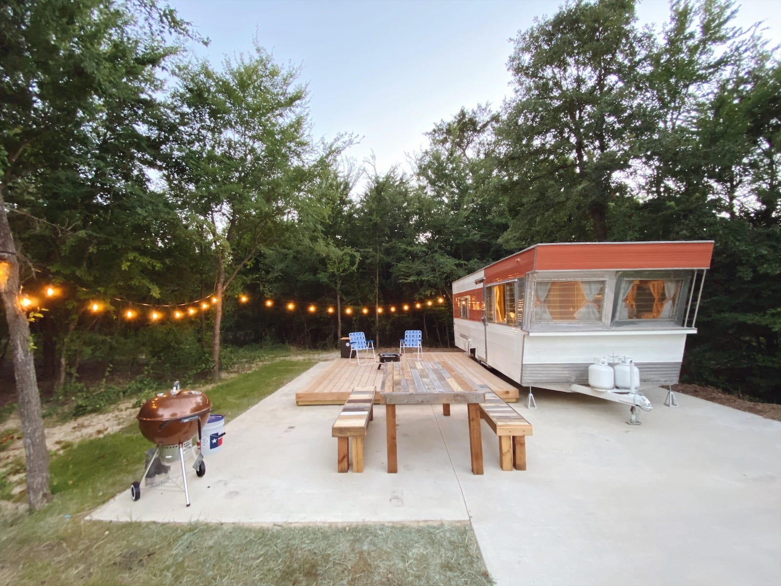 Vintage travel trailer surrounded by trees and a string of lights with wooden deck and wood table and grill