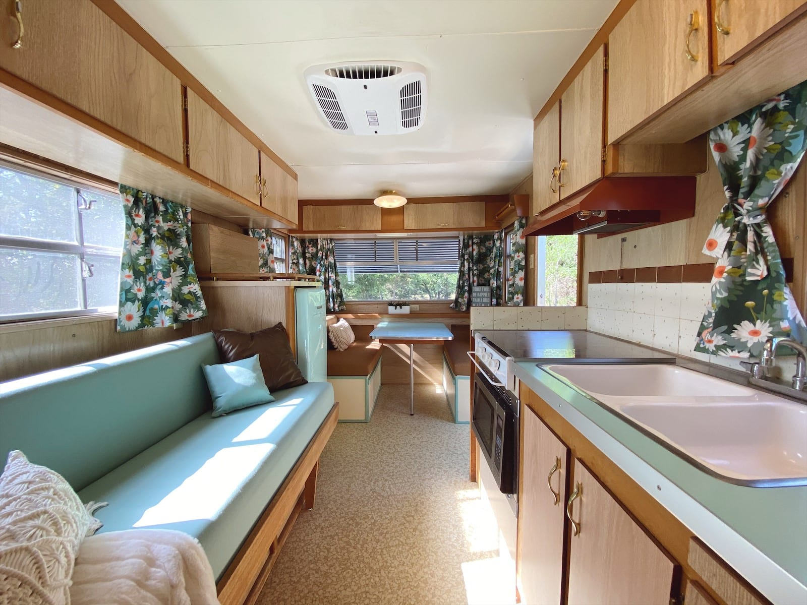 1965 Bloes Aero renovated airstream featuring mint green interior with couch and kitchen and dining area.